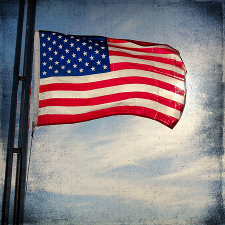 The American Flag Flapping Against A Blue Sky On A Flag Pole.