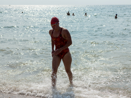ODESSA, UKRAINE - August 21, 2018: The swimmers finish at the Race Nation. Athlete triathlete swimmer. Professional athlete in triathletes trains for an ironman. Sportsman beautifully floats in sea at competitions