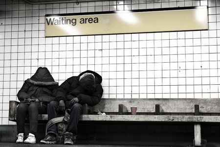 New-York, USA - November 14th, 2012: Two anonymous ault people sitting on a bench at a subway station's designated waiting area, hidden behind their coats, appear to be sleeping.
