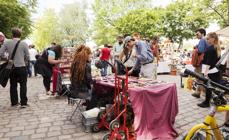 Berlin, Germany - June 10th, 2012: Large amount of people walking in the Sunday flee market held at Mauer Park. Homemade knives are displayed for sale in the foreground table.