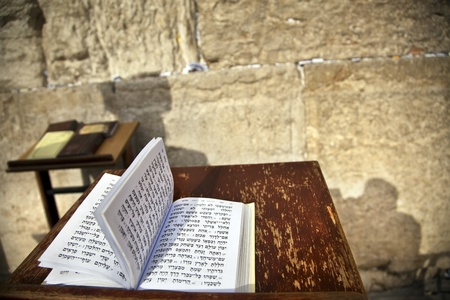 The biblical Book of Psalms opened on one of the pages of the morning prayer, resting on a pedistal . There's also a shadow of a Jewish orthodox man on the wailing wall in the background.Shot in the western wall in the old city of Jerusalem.