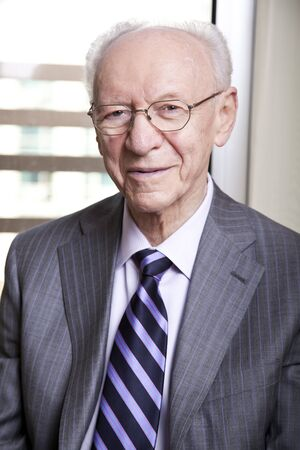 Medium close-up portrait of a senior businessman (in his 80's) smiling to the camera wearing a suit and tie, as well as old fashion glasses.