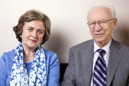 A high society senior couple (he's in his 80's, she's in her late 60's) sitting on a sofa looking at the camera. Medium close up.