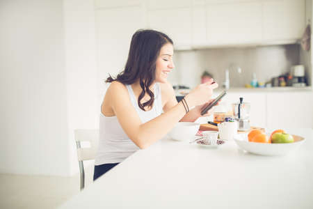 Foto de Young brunette is reading the newspaper while having breakfast at home.Modern woman lifestyle-healthy fitness breakfast,coffee and fruit,reading motivational quotes.Starting your day,positive energy - Imagen libre de derechos