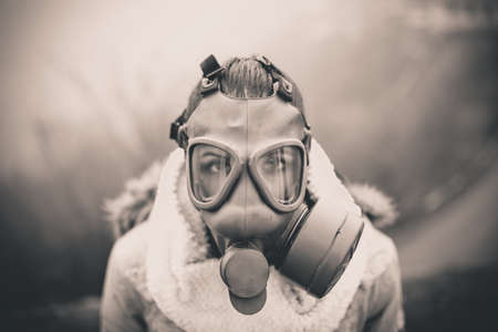 Environmental disaster.Woman breathing trough gas mask,health in danger.Concept of pollution,apocalypse.Polluted air,environmental problems.Riot with gas mask.Smog,poisonous particles,bio hazard