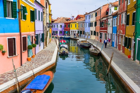 Burano canal full of boats and colorful houses.