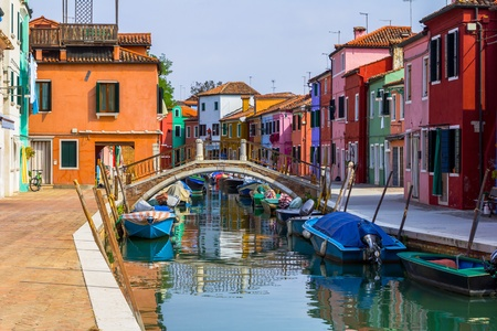 Burano street full of boats and the typical colorful houses.