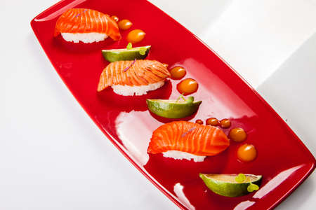 Sushi on red plate served with lime. Isolated on white.