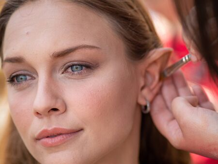 Photo pour Makeup on the ears to a model to turn her into an elf - image libre de droit
