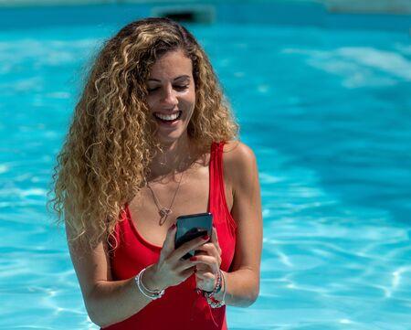 Photo pour Blonde girl uses mobile phone inside the pool - image libre de droit