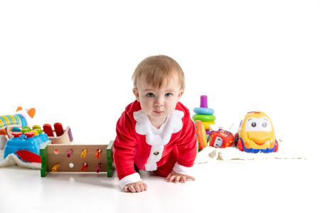 Photo for Stock studio photo with white background of a baby dressed like Santa crawling in the middle of plastic toys. Portrait - Royalty Free Image