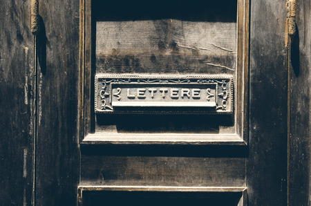 Old italian letter box on a vintage rustic wooden door