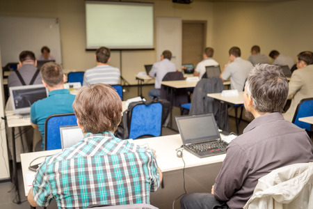 Photo for Rear view of people attentively listening to teacher in the classroom - Royalty Free Image