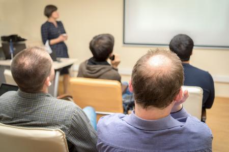Foto de Back view of an adult students audience listening the presentation of a woman teacher near the screen - Imagen libre de derechos