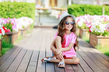 Foto de Fashion girl wearing a pink checkered shirt, hat and sunglasses in city. - Imagen libre de derechos