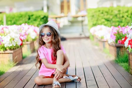 Foto de Fashion little girl model wearing a pink checkered shirt, hat and sunglasses in city. - Imagen libre de derechos