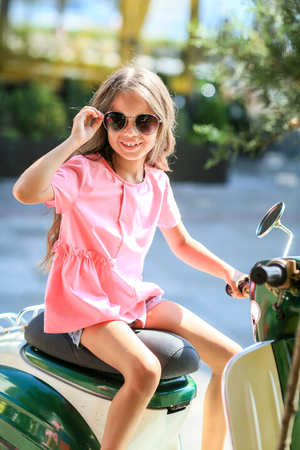 Foto de Fashion kid summer in the city stands on a streetl. Trendy girl in sunglasses standing on the street at sunset - Imagen libre de derechos