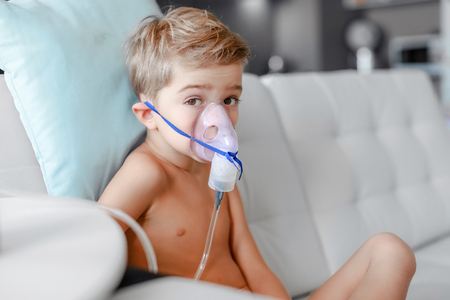 Photo pour sick boy in nebulizer mask making inhalation, respiratory procedure by pneumonia or cough for child, inhaler, compressor nebulizer, nebules machine for health care. Kid catch cold. - image libre de droit