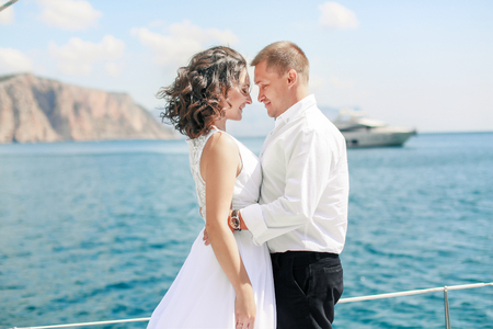 Photo pour A Just married couple on yacht. Happy bride and groom on their wedding day. - image libre de droit