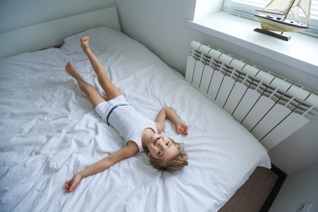 Foto de Happy boy playing in white bedroom. Little boy brother play on the bed wearing pajamas. Family at home jumping on the bed and lying - Imagen libre de derechos