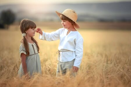 Photo pour Two children a boy and a girl of preschool age walk together in a wheat field. - image libre de droit