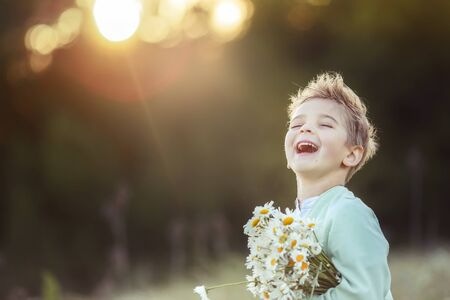 Photo pour Boy blond child close up with a bouquet of daisies in his hands on a blurred background outdoors. - image libre de droit