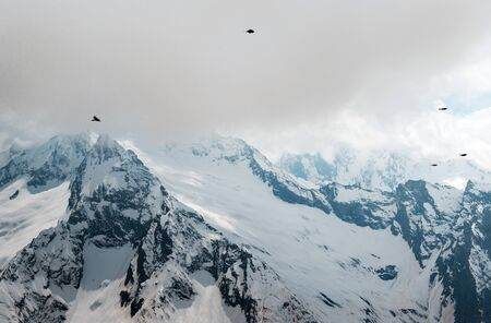 birds in the sky with clouds over mountain slopes, mountains under snow, winter, Caucasus, mountain landscape,