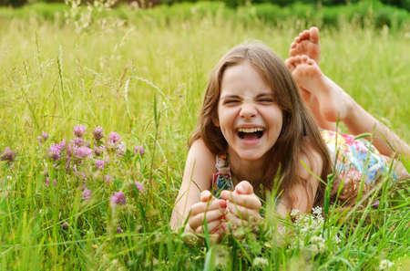 Photo for girl of 10 years old lies on the grass among the flowers and laughs - Royalty Free Image