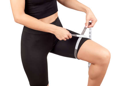 Photo pour a young beautiful woman in a black tracksuit measures the volume of the thigh with a centimeter tape, isolate on a white background - image libre de droit