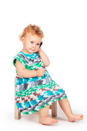 Photo pour a little girl with curly hair and a phone on a white background - image libre de droit