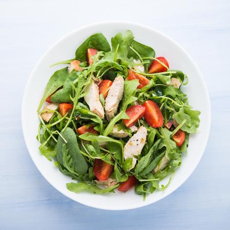 Foto de Fresh salad with chicken, tomato and greens (spinach, arugula) on blue wooden background top view. Healthy food. - Imagen libre de derechos
