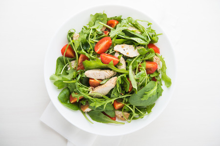 Photo for Fresh salad with chicken, tomato and greens (spinach, arugula) top view. Healthy food. - Royalty Free Image