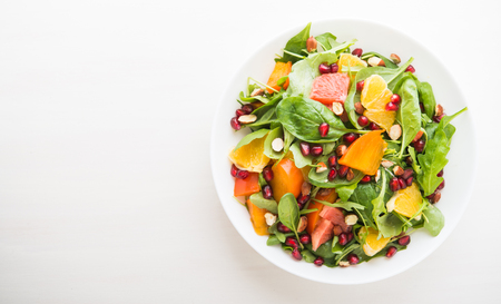 Fresh salad with fruits and greens on white wooden background top view with space for text. Healthy food.