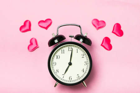 Alarm clock on a pink background, symbolically ringing the hearts. The concept of the time of love, the time of date, the wedding, the day of St. Valentine