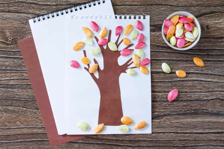 Autumn tree with colorful different leaves pumpkin seeds on a wooden background. Children\'s art project, craft for children. Craft for kids.