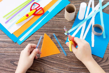 Foto de The child cuts out the details of a paper boat, congratulations concept of Father's Day. Glue, scissors and paper on a wooden table. Children's art project craft for kids. Craft for children. - Imagen libre de derechos