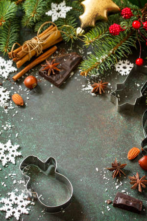 Foto de Ingredients for Christmas Gingerbread baking - chocolate, cinnamon, anise and nuts on dark a stone or slate background. Seasonal, food background. Copy space. - Imagen libre de derechos