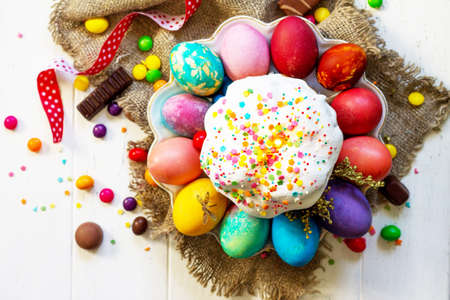 Photo for Festive composition in rustic style, Easter meal Breakfast. Easter cake and painted eggs on white wooden table. Top view flat lay background. - Royalty Free Image