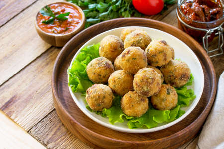 Photo for Arancini. Italian Rice Balls with Mozzarella and Sun-dried tomatoes, with tomato sauce on wooden table. Copy space.  - Royalty Free Image