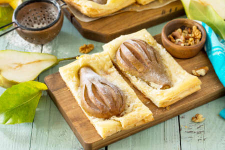 Photo pour Summer dessert. Homemade Cake Puff Pastry with Pear and Stuffed with Nut Cream a rustic wooden table. - image libre de droit