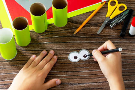 Foto de Child draws details Paper Roll Pencil Holder the new school year. Welcome back to school. Children's Art Project, needlework, crafts for kids. - Imagen libre de derechos