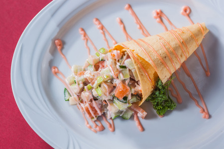 salad in a waffle cone sauce and greens on a round white plate