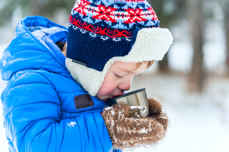 Outdoor portrait Happy child drinking hot tea from a thermos in winter park