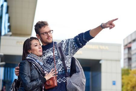 two happy tourists couple searching location together with a phone and map and pointing with the finger.の写真素材