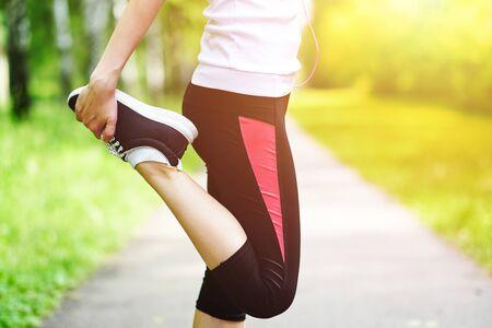 Foto de young fitness woman runner stretching legs before run on grass. - Imagen libre de derechos