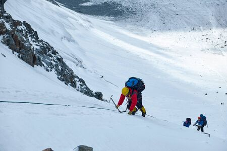 Photo pour Bunch of mountaineers climbs to the top of a snow-capped mountain - image libre de droit
