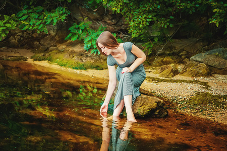 Attractive young woman wearing long dress sitting on the rock with feet in a weedy pond water