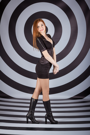 Full length studio portrait of beautiful slim woman in short black dress and high leather boots standing in front of target background