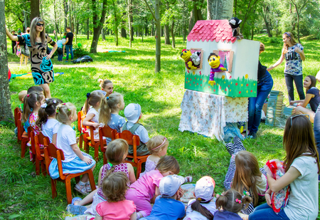 Zaporizhia/Ukraine- June 5, 2016: children watching puppet show, sitting on the small chairs and laying on the grass in the park on charity family festival organized in regions with most quantity of refugees from Donetsk area, occasioned with Internationa