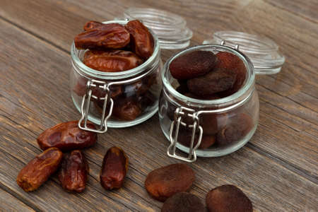 Photo pour Organic bio dried dates and dried apricots, apricot in glass jars stand on an old rustic wooden table. Dried fruits. Healthy snack - image libre de droit
